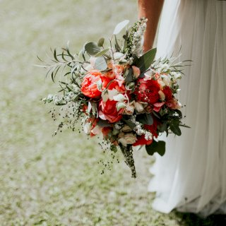 Coral peonies and roses in bridal bouquet
